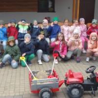Grupa dzieci siedzących na ławce w gospodarstwie
